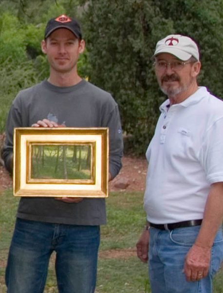 """Dan Schultz receives first place award for his """"Light through the Trees"""" painting from award judge Skip Whitcomb at the Glen Eyrie Plein Air Paint Out in Colorado Springs, Colorado."""