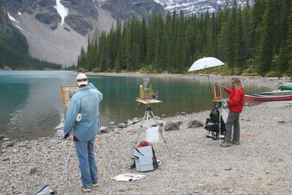 Hermann Brandt and Liz Wiltzen painting with Dan Schultz at Moraine Lake in Banff National Park, Canada