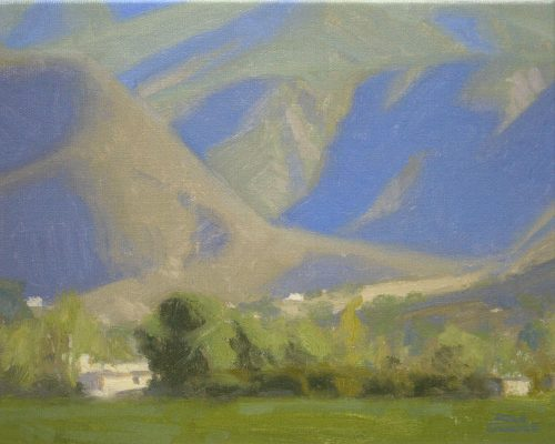 Ojai Mountain Shadows, giclee print by Dan Schultz. Large mountains with blue and violet shadows rise behind a green foreground.