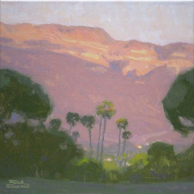 Ojai Pink Moment, giclee print by Dan Schultz. Pink sunset light on Topa Topa Bluff in the Ojai Valley, with Palm trees and other trees in the foreground.