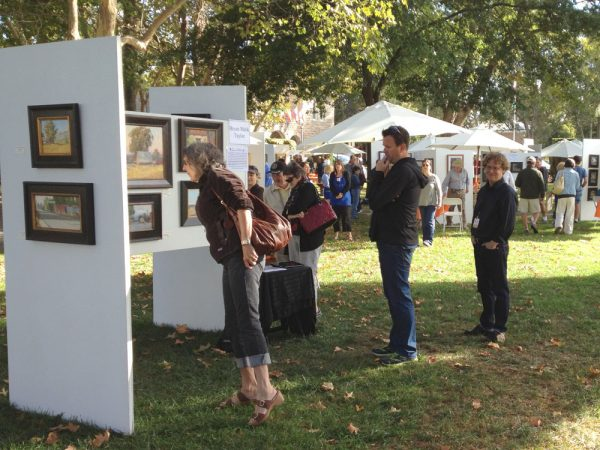 Artist Bryan Mark Taylor at his booth with interested customers at Sonoma Plein Air 2012.