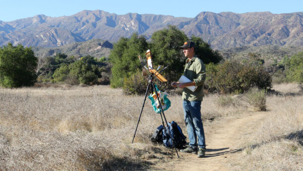 Dan Schultz painting outdoors in California with his Open Box M pochade box mounted on a camera tripod.